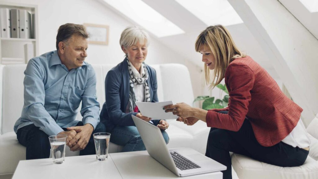Mature Couple Meeting with Financial Advisor. They are listening to financial advisor. She is speaking about retirement and insurance options for them. Holding contract in her hands and explaining to clients.